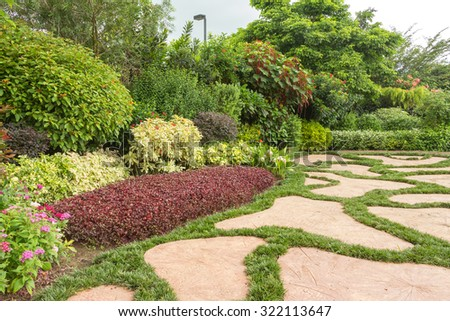 Landscaped garden with flowerbed and colorful plants - stock photo