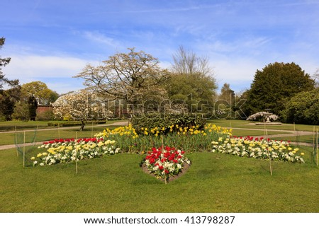 Landscaped park with flower beds and blossoming trees in springtime. - stock photo