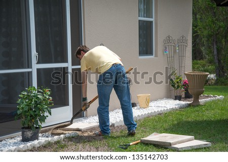 Landscaping Work - A man working outdoors.  He is using a shovel to level the dirt to place concrete patio slabs in the landscaping near the door to the house. - stock photo