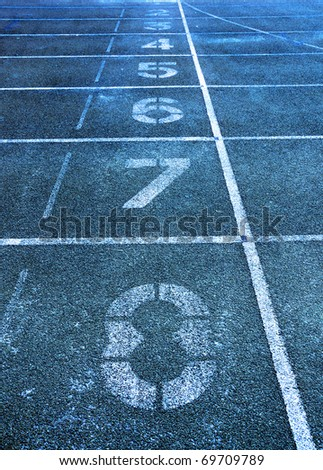 Lanes of a blue race track with numbers at high school - stock photo