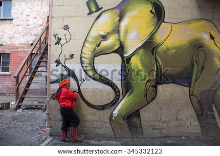 LANGA TOWNSHIP, SOUTH AFRICA - JULY 12, 2015 - A young boy poses for a photograph next to a painted building in Langa, South Africa, a township located on the outskirts of Cape Town. - stock photo