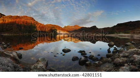 Langdale Pikes reflected in Blea Tarn at dawn in the English Lake District - stock photo