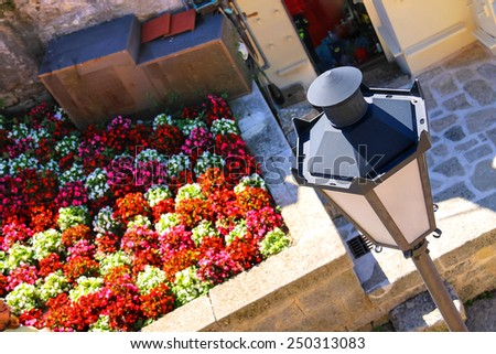 Lantern and blooming flower bed on terrace in front of the house - stock photo