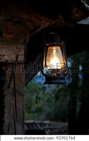 Lantern hang in front of wooden house in the night - stock photo