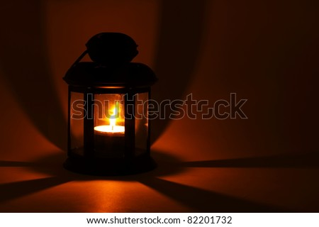 Lantern with alight candle in the dark - stock photo
