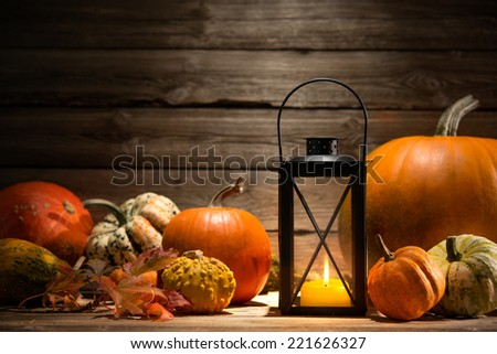 Lantern with candle, pumpkins and autumn decorations on old wooden - stock photo