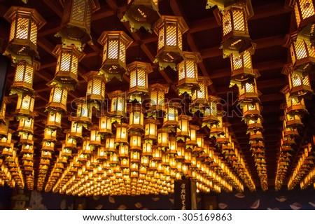 Lanterns hanging on buddhistic temple roof on Miyajima, Japan - stock photo