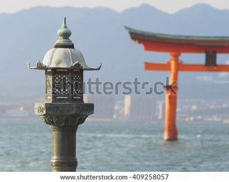 """Lanterns of Shrine on seaside place. Background is big Shrine's gate """"Torii"""" on sea, Itukushima Shrine, Hiroshima, Japan. - stock photo"""