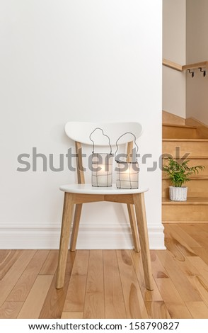 Lanterns on a white chair, in a room with staircase. - stock photo