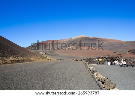 LANZAROTE, CANARY ISLANDS - JANUARY 07, 2014: Unidentified tourists taking a camel ride in Timanfaya National Park, Lanzarote, Canary Islands, Spain - stock photo