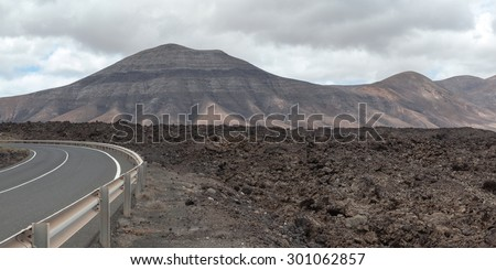 Lanzarote volcanic landscape: huge fields of lava material and some volcanoes in between. Almost 300 years since the eruption, but majority of the land is still barren land. - stock photo
