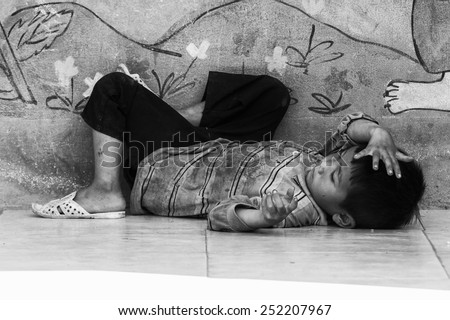 LAO CHAI VILLAGE, VIETNAM - SEP 22, 2014: Unidentified Hmong little  boy lays on the ground on a break in a local primary school. Hmong is on of the minority eethnic group in Vietnam - stock photo