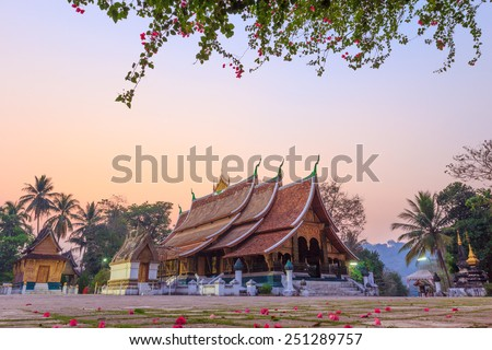 Laos Heritage state at Wat Xieng Thong luang prabang Laos, Flowers in front of Wat Thong Xieng temple - stock photo
