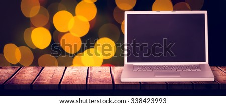 Laptop against desk with christmas tree in background - stock photo