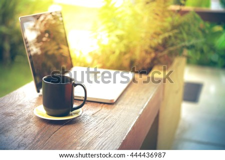 laptop and black coffee cup on wood in cafe - stock photo