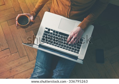 Laptop and coffee cup in girls hands sitting on a wooden floor - stock photo