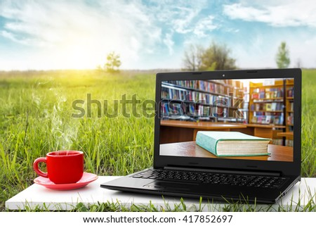 Laptop and cup of hot coffee on the background picturesque nature, outdoor office. E-book library concept with laptop computer and book. Old books on a wooden shelf. Travel concept. Business ideas. - stock photo