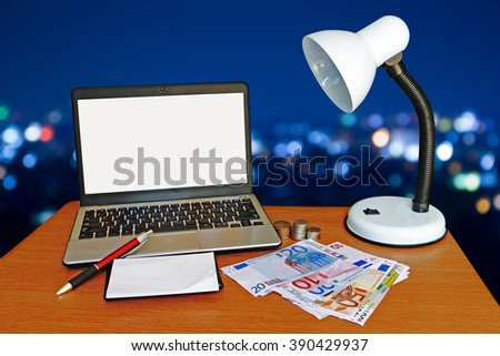 laptop and money with blur light in city background - stock photo