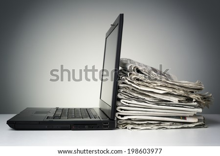 Laptop and newspaper concept for internet and electronic online news - stock photo