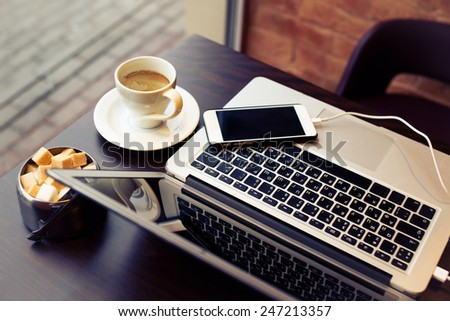 Laptop and phone on the table with cup of coffe and sugar cane - stock photo