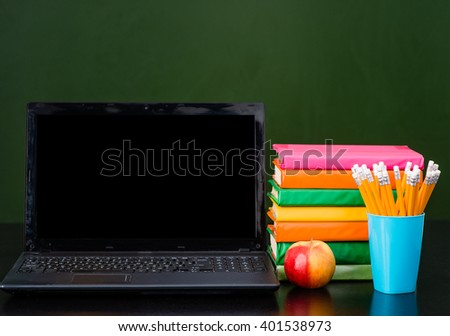 Laptop and pile of books near empty green chalkboard. Sample for text - stock photo