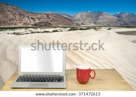 laptop and red mug on wood table with desert in  india - stock photo