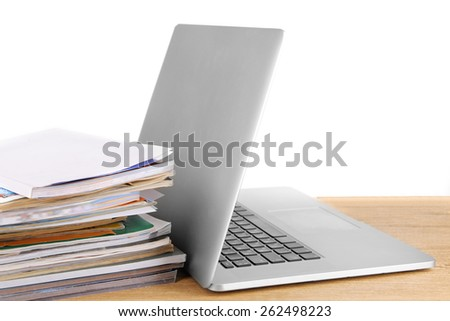 Laptop and stack of magazines on table isolated on white - stock photo