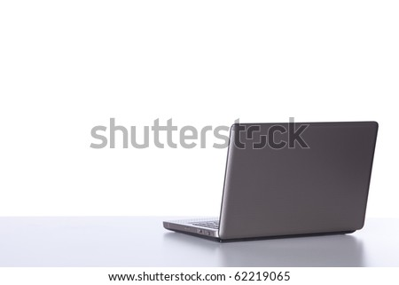 Laptop at the desk in the office isolated on white - stock photo