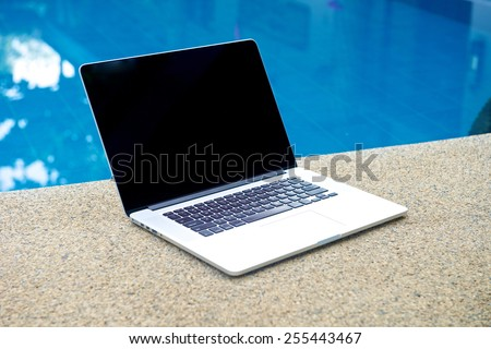 Laptop by the pool, working on vacation with mobility concept - stock photo