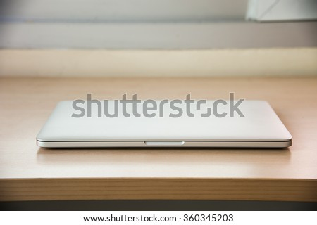 Laptop close on wood table - stock photo
