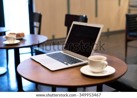 Laptop computer and coffee cup on wooden table  - stock photo