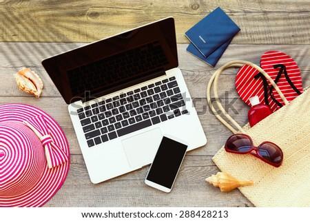 Laptop computer and smart phone with beach accessories on wooden board - stock photo