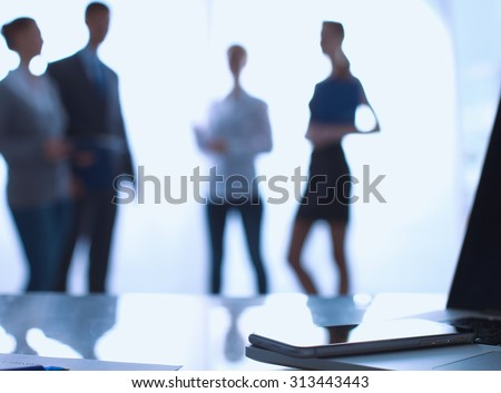Laptop  computer on  desk ,  businesspeople standing in the background - stock photo