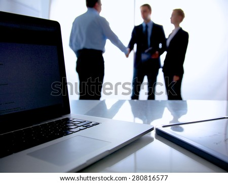 Laptop  computer on  desk , three businesspeople standing in the background - stock photo