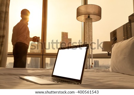 Laptop computer on white bed sheets in cozy room with copy space blank screen. Young businessman with cup of coffee standing at window looking at city scenery on the background. Motivation concept - stock photo