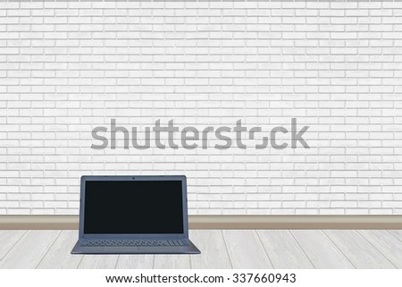 Laptop computer on white wood floor and white brick wall background - stock photo