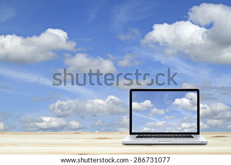 Laptop computer on wooden floor with sky  background. - stock photo