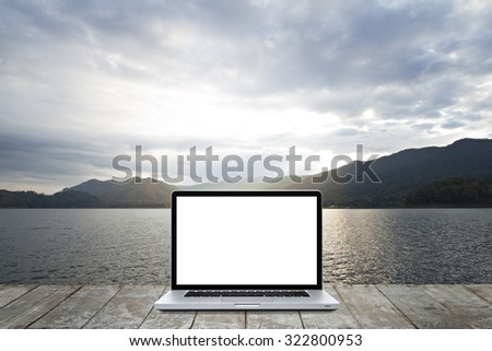 Laptop computer on wooden with morning environment of lake and  mountain  background. - stock photo