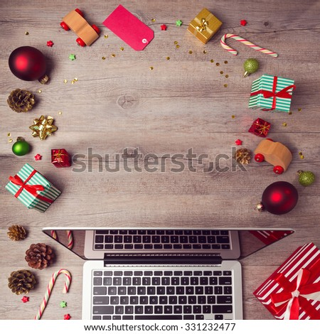 Laptop computer with Christmas decorations on wooden background. Christmas mock up template. View from above - stock photo