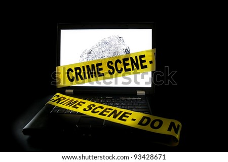 Laptop computer with crime scene tape across it - stock photo