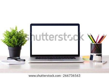 laptop computer with isolated screen stands on the table in the office with phone and watch - stock photo