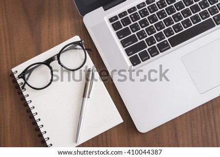 Laptop computer with note book on wooden table - stock photo