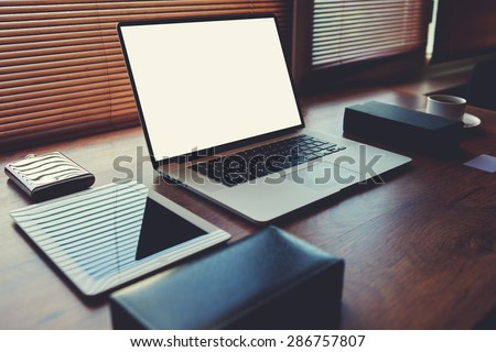 Laptop computer with white blank copy space screen for text message or publicity content lying on wooden table with digital tablet and stylish accessories,electronic business and distance work concept - stock photo