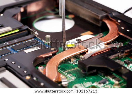 Laptop cooling system repairing process with screw driver - stock photo