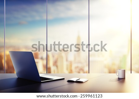 laptop, cup and diary on table in office at sunrise - stock photo