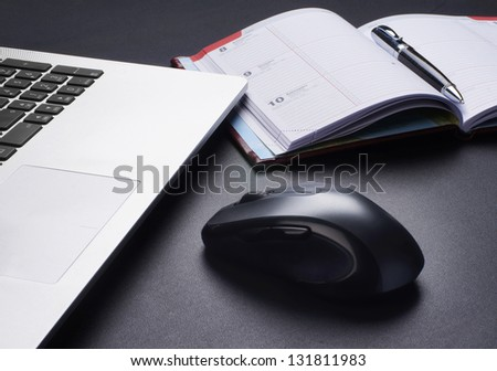 Laptop, mouse and the diary on the table - stock photo