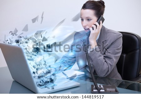 Laptop of a businesswoman exploding while she is on the phone - stock photo