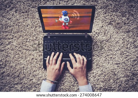 Laptop on the floor. Woman hands typing on the keyboard. Robot and wifi icon on the screen. - stock photo