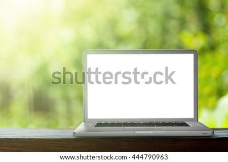 laptop on the green bokeh backrounds. Like ipade - stock photo