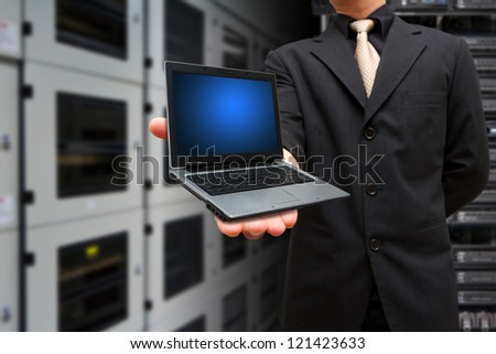 Laptop on the hand in data center room - stock photo